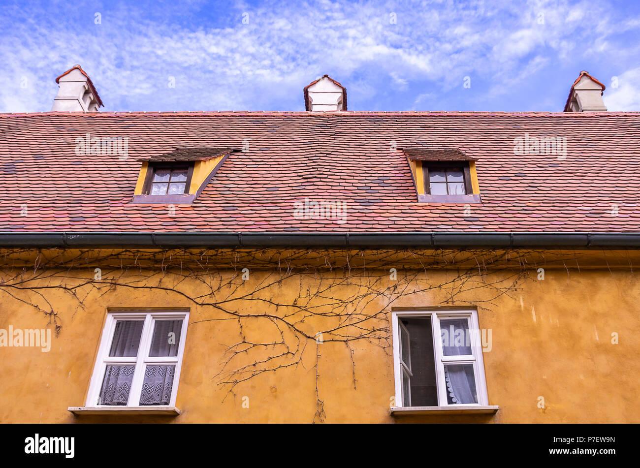 Augsburg, Bayern, Deutschland - 10. September 2015: Typische Obergeschoss Fassade und das Dach eines der armenhäusern in der Fuggerei sozialen Wohnungsbau. Stockfoto