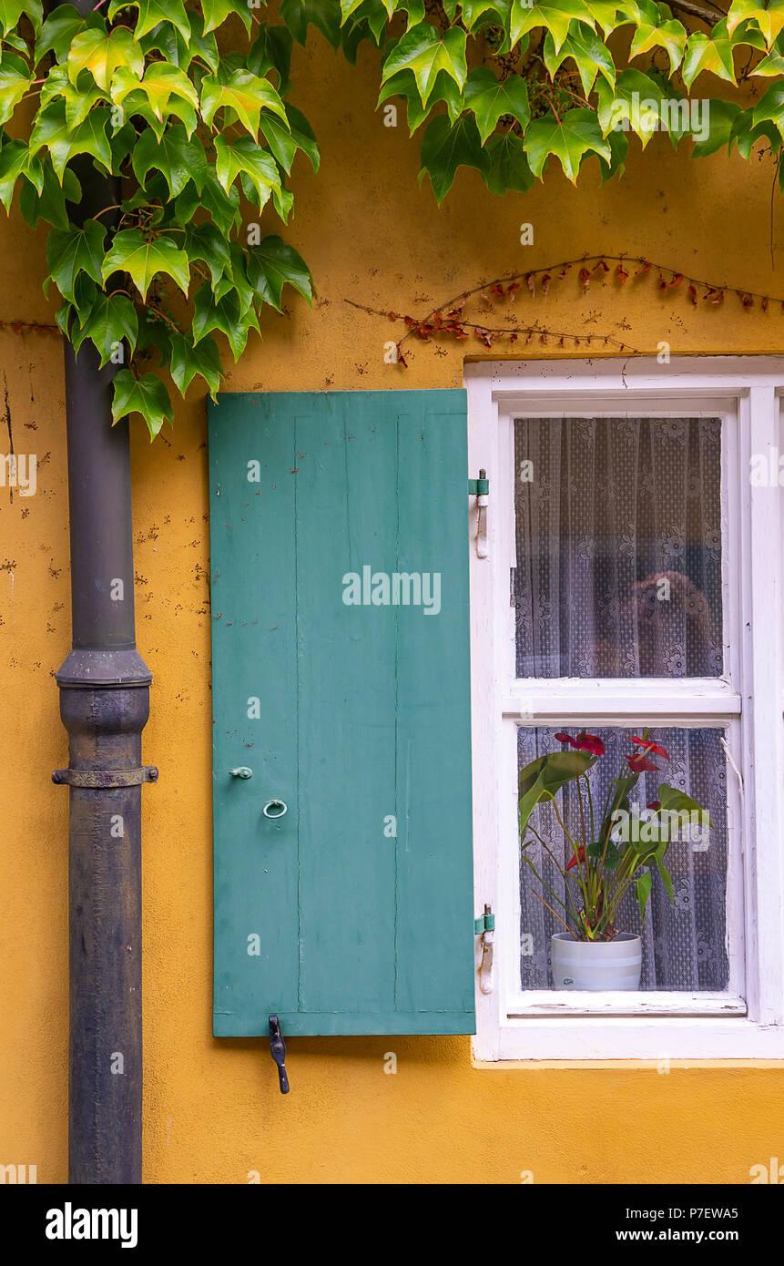 Augsburg, Bayern, Deutschland - 10. September 2015: Typische Fenster mit Fensterläden auf eines der Häuser in der Fuggerei sozialen Wohnungsbau. Stockfoto