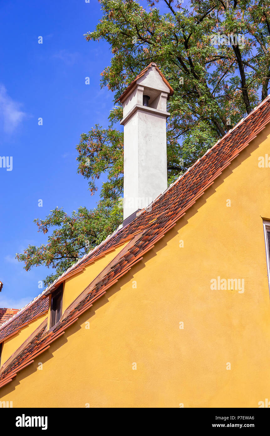 Augsburg, Bayern, Deutschland - 10. September 2015: Blick auf typische Dach Architektur mit Kamin in der Fuggerei sozialen Wohnungsbau. Stockfoto