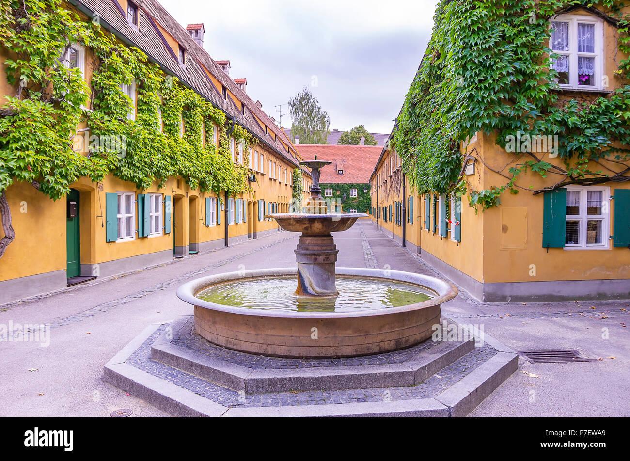 Augsburg, Bayern, Deutschland - 10. September 2015: Brunnen in der Herrengasse Gasse in die Fuggerei sozialen Wohnungsbau. Stockfoto