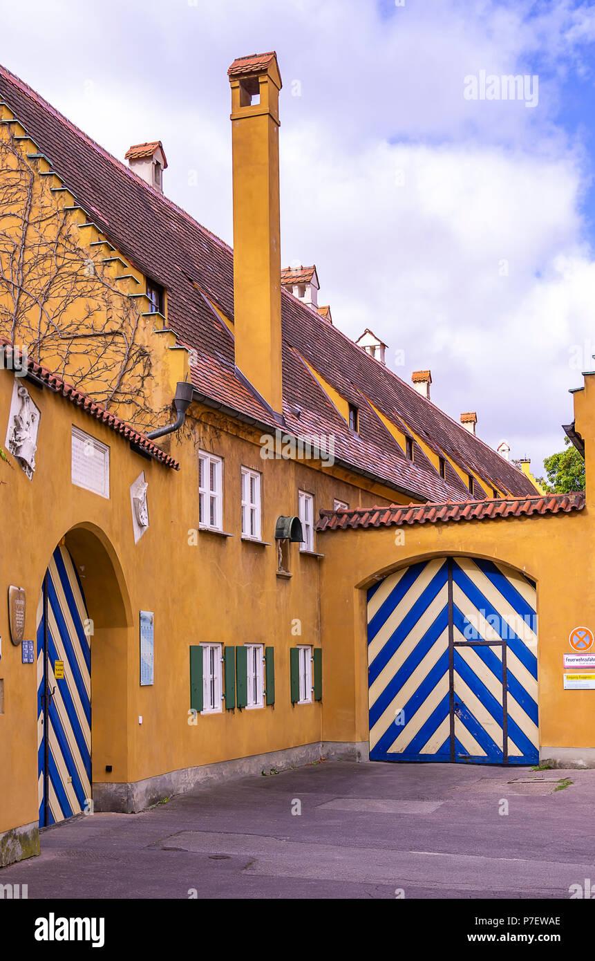 Fuggerei, Augsburg, Bayern, Deutschland - Außenansicht des Gebäudekomplexes mit Toren an Jakob's Square (jakobsplatz). Stockfoto