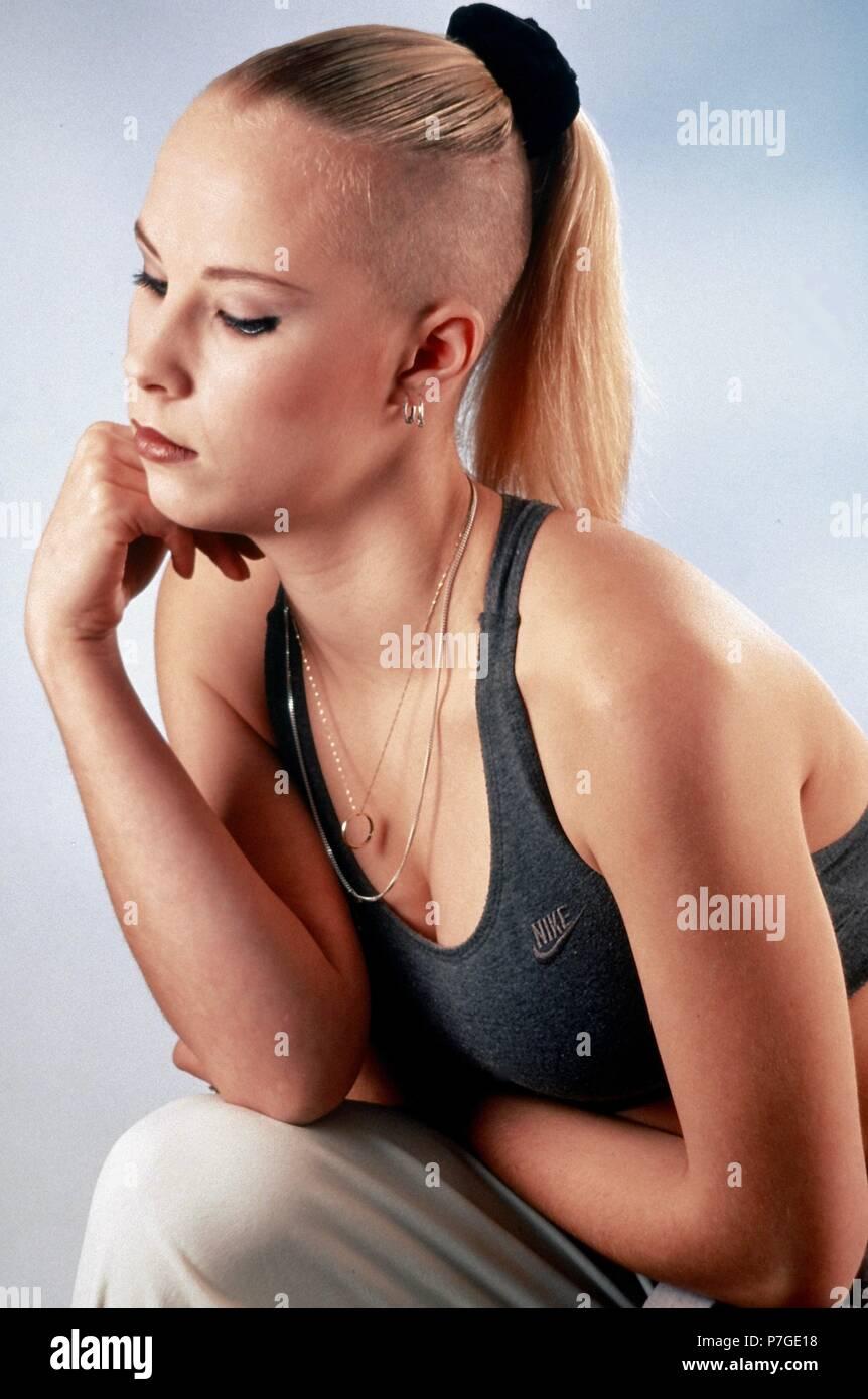 100-004-092 1990 s gabber Kultur - junge Frau mit Nike Kleidung und Kopf rasiert Stockbild