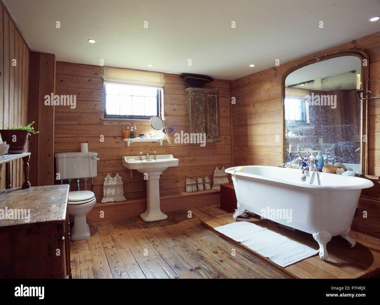 holzgetäfelte wände und boden im bad mit großen antiken spiegel über