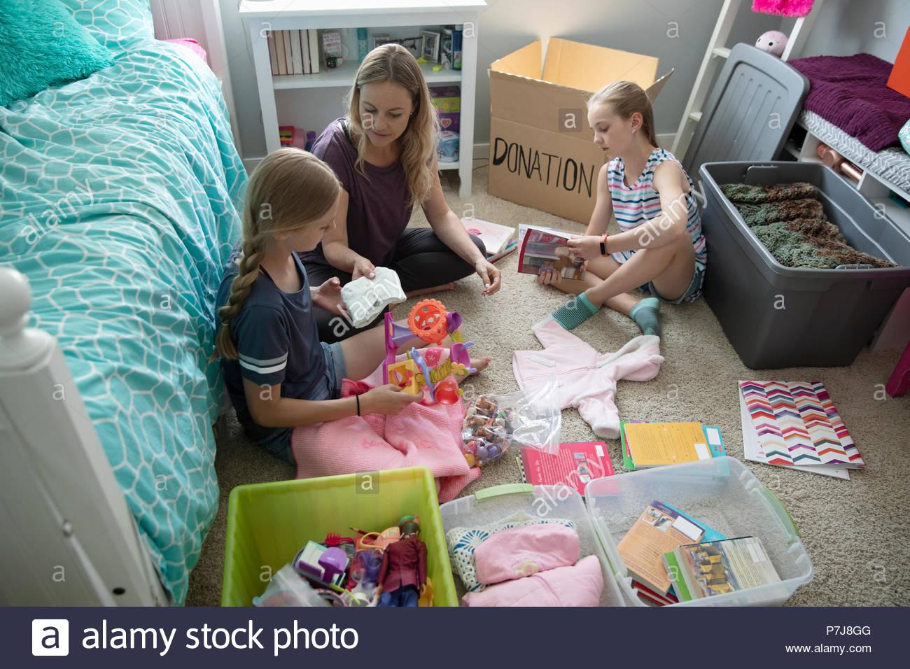 Mutter und Töchter spenden Baby Kleidung im Schlafzimmer Stockbild