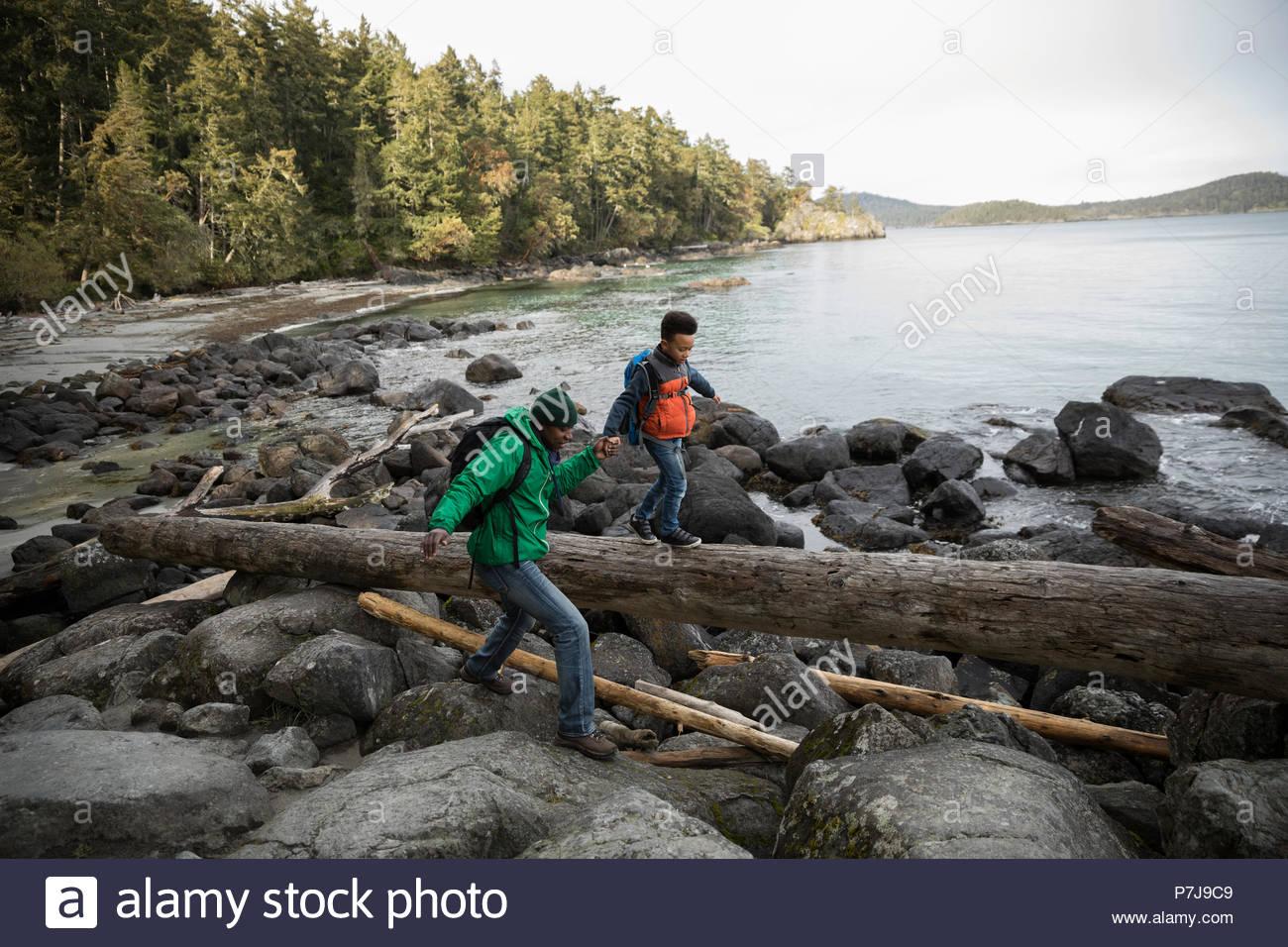 Vater und Sohn über Felsen und gefallenen Log auf robusten Strand Stockbild