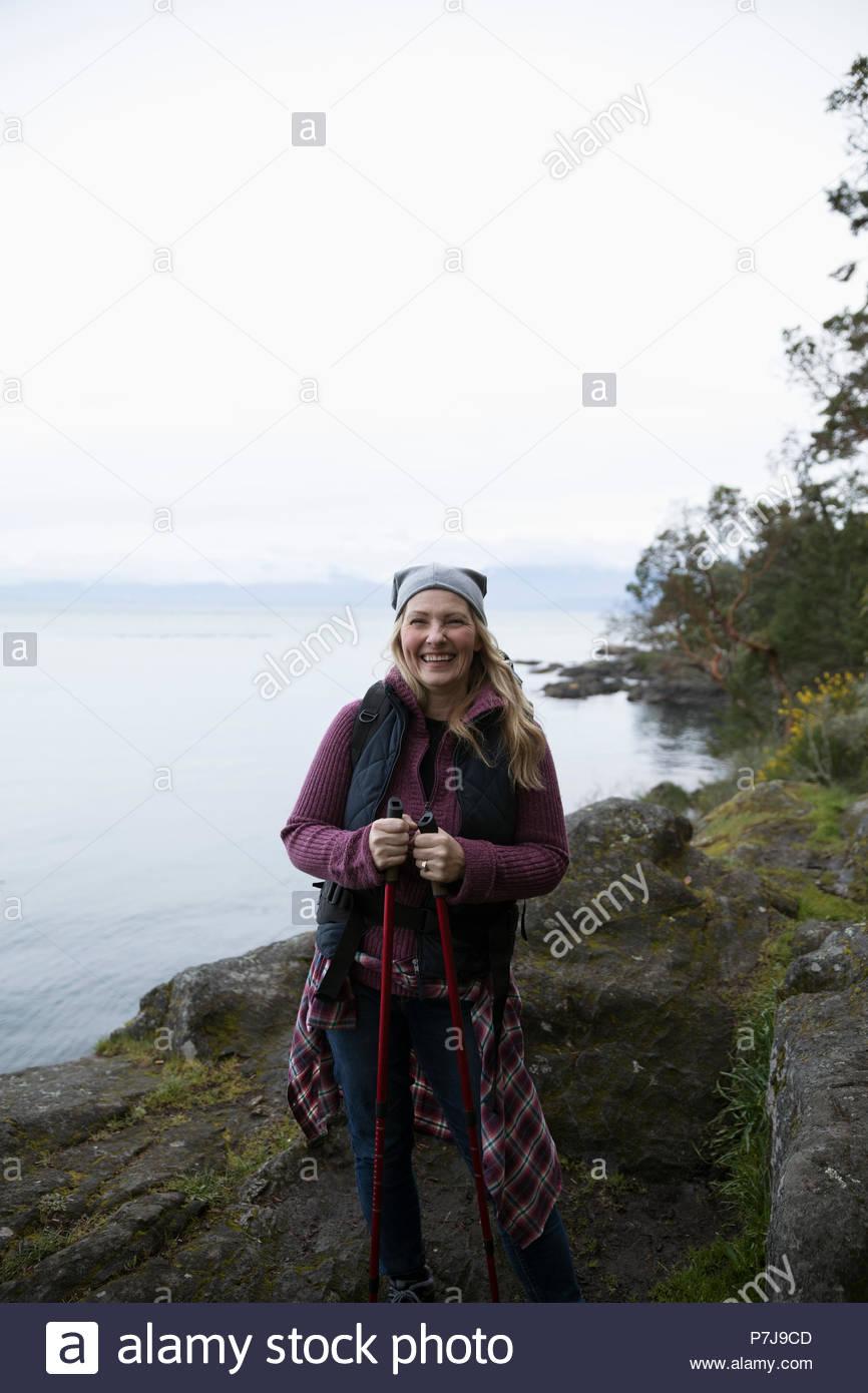 Porträt Lächeln, unbekümmerte Frau Rucksack am Ocean Stockbild