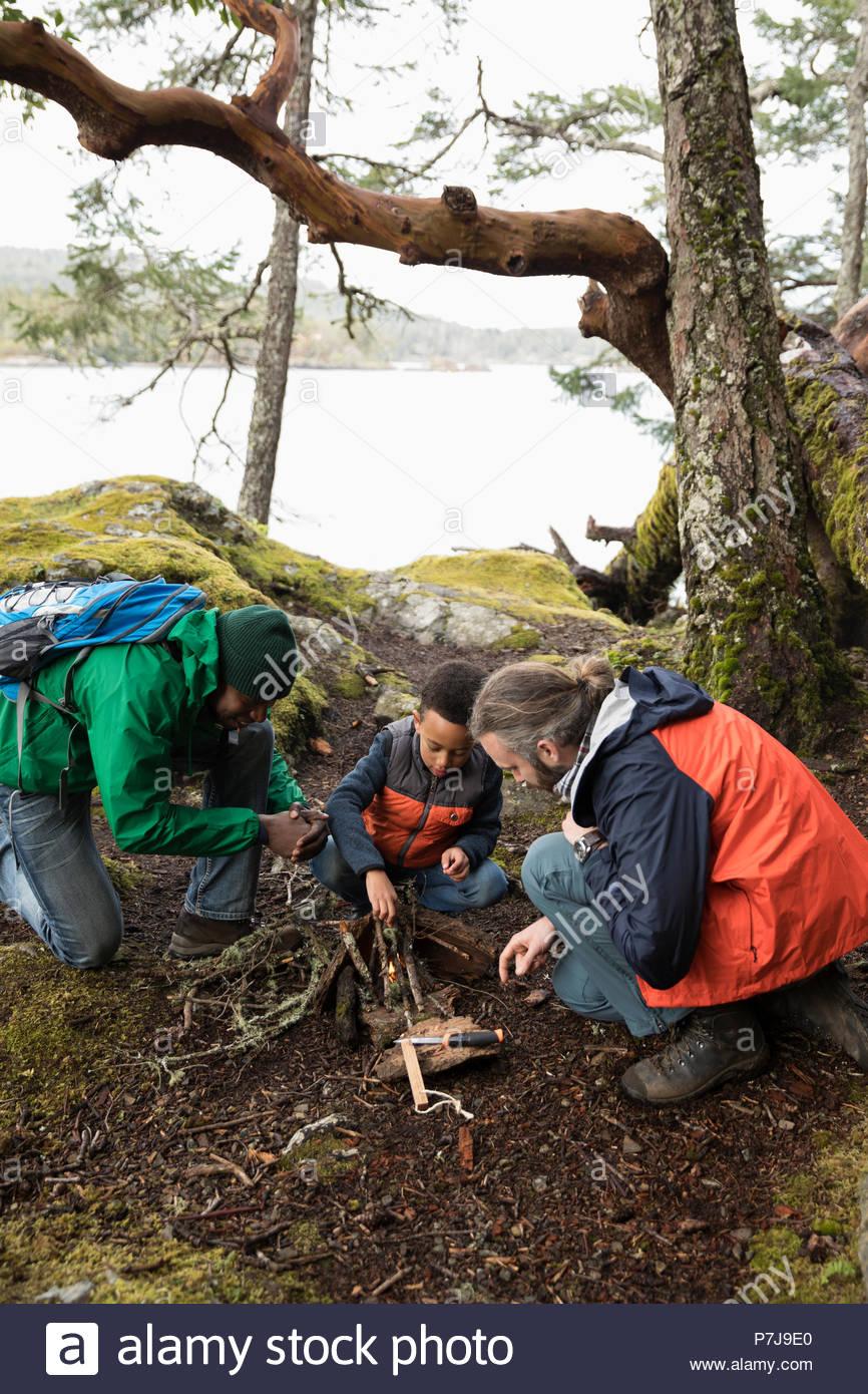 Trail Guide lehre Vater und Sohn wie Lagerfeuer im Wald zu bauen Stockbild