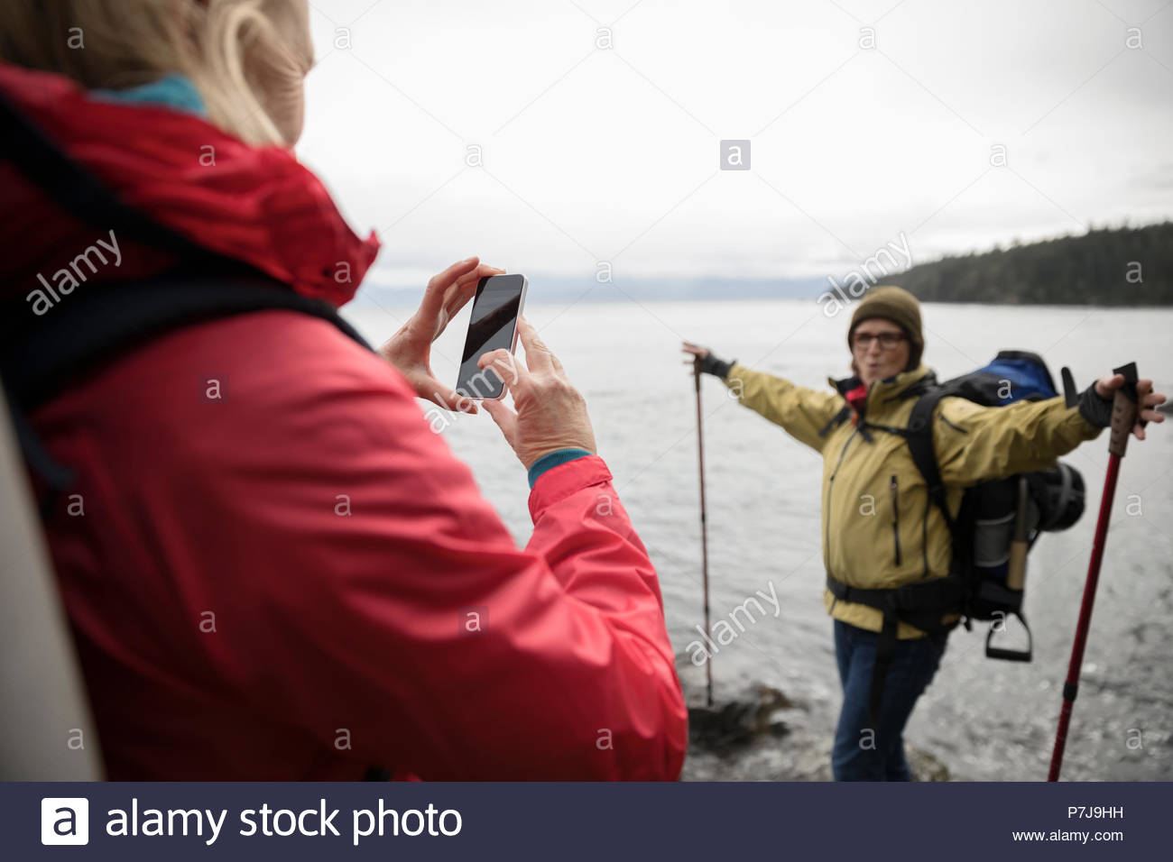 Active Senior Frau fotografieren exuberant Freund Rucksack am Ocean Stockbild