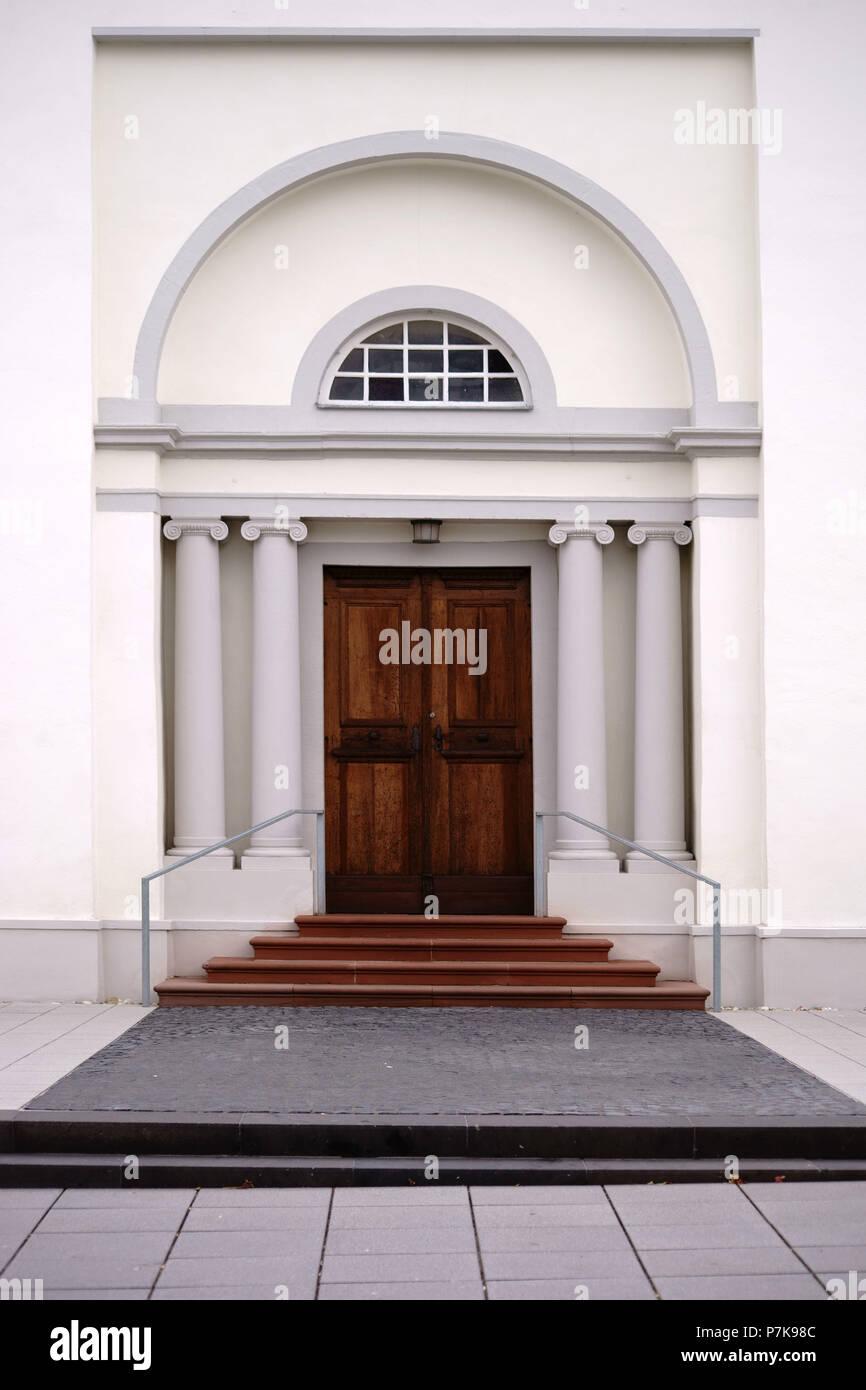 Eingang einer neu gebauten und moderne Kirche mit einer Eingangstür mit Rundbogen und weißen Wänden Stockbild