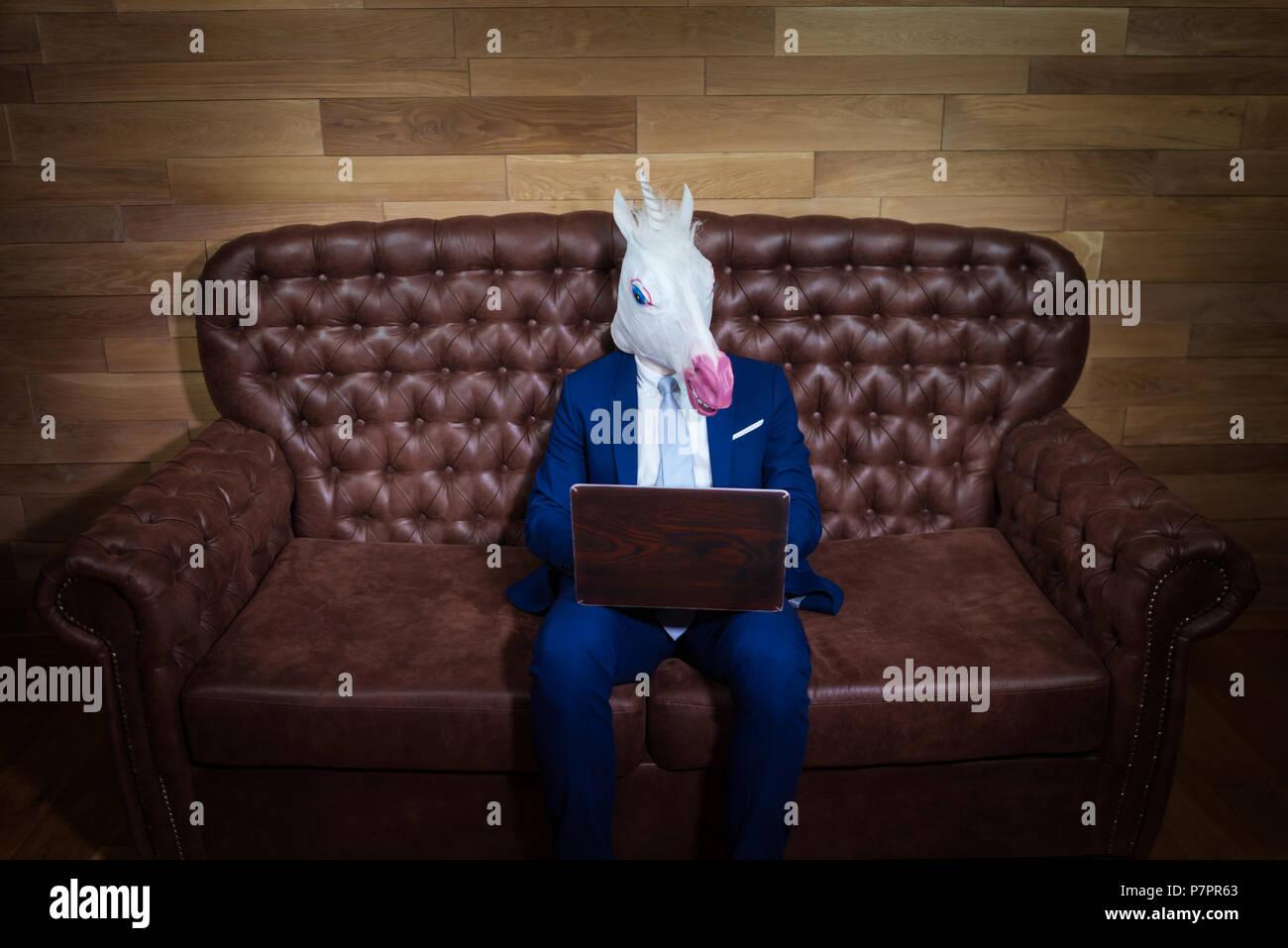 Fremder Mann Im Eleganten Anzug Zu Hause Arbeiten Im Buro Ungewohnliche Junge Manager In Komischen Maske Lustige Einhorn Sitzt Auf Einem Sofa Wie Boss Stockfotografie Alamy