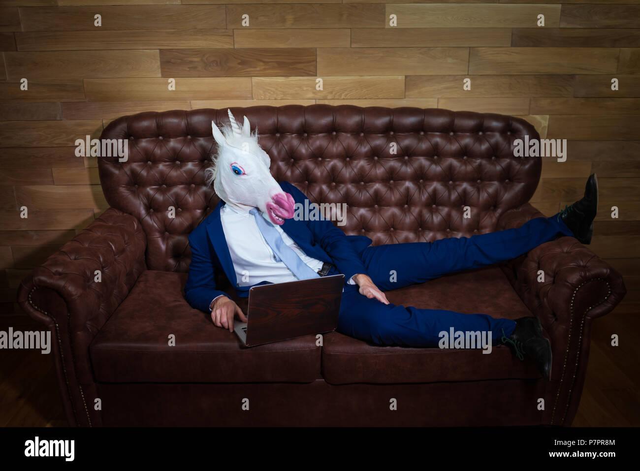 Fremder Mann Im Anzug Zu Hause Arbeiten Im Buro Ungewohnliche Junge Manager In Komischen Maske Auf Dem Hintergrund Der Holzernen Wand Lustige Einhorn Sitzt Auf Einem Sofa Wie Ein Chef Stockfotografie