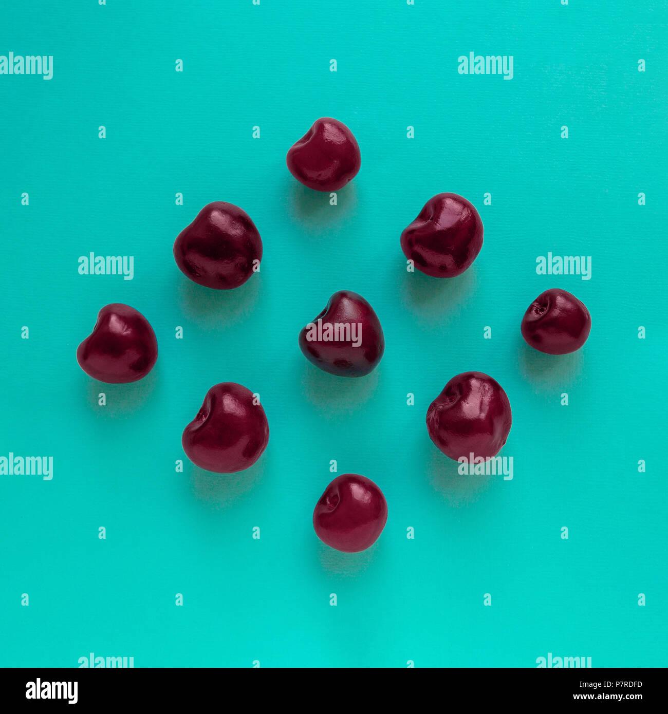 Cherry Draufsicht reifen Kirschen liegen in der Rautenform auf blauem Hintergrund Flach Foto Stockbild