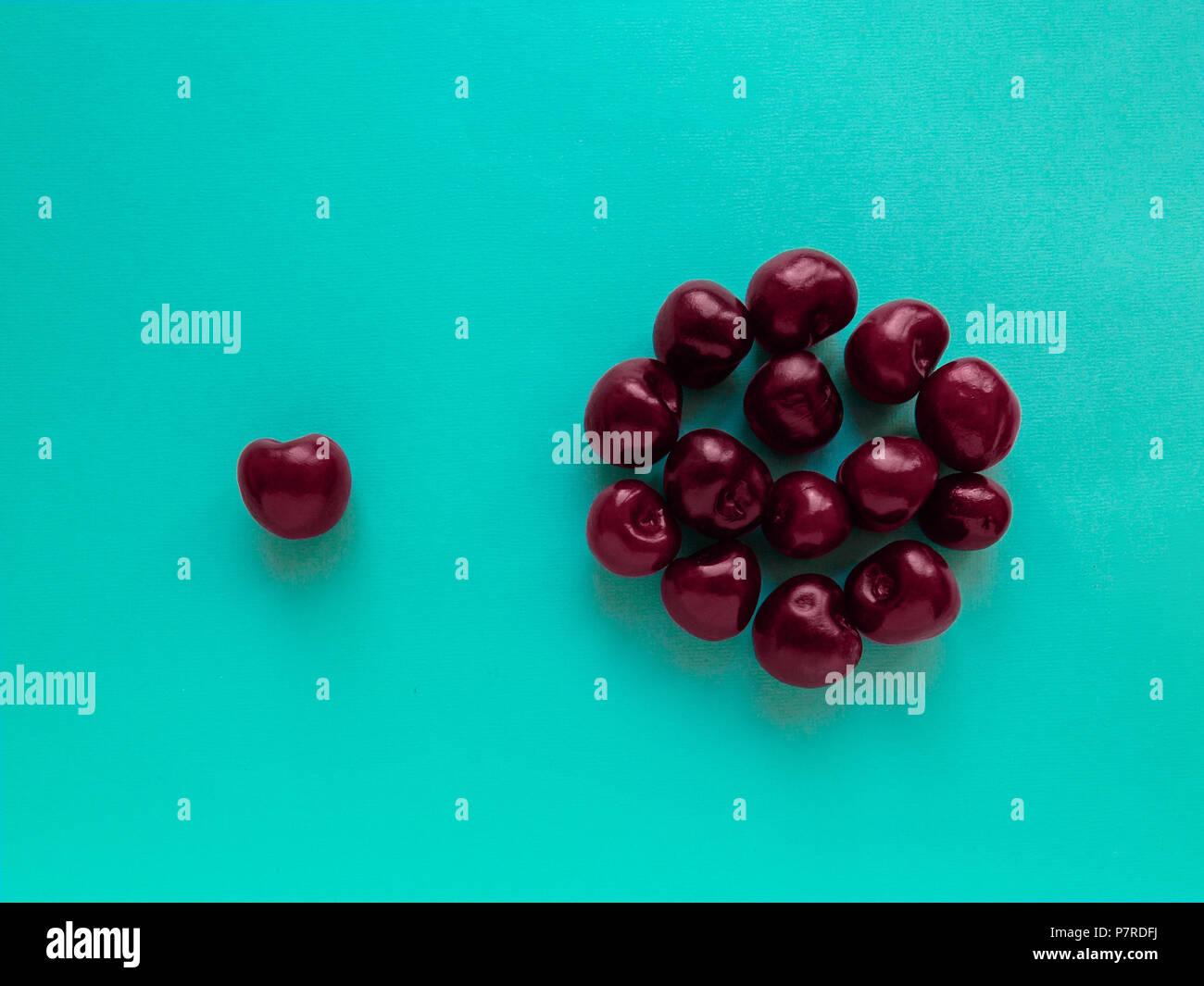 Cherry Draufsicht Viele reifen Kirschen in die runde Form auf blauem Hintergrund liegen flach Foto Stockbild