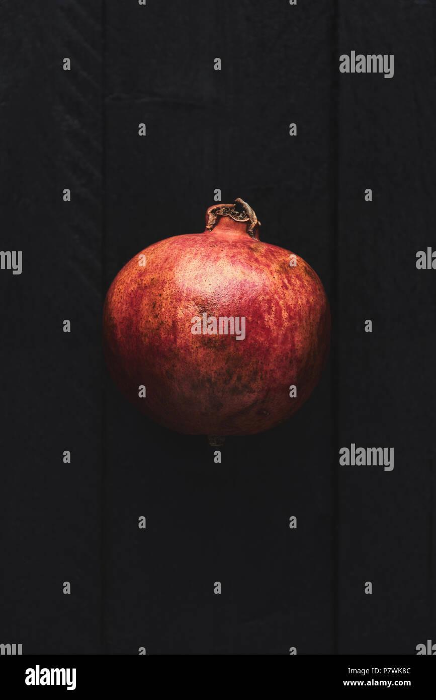 Flach reifer Granatapfel Obst auf schwarzem Holz- vintage Hintergrund. Ansicht von oben mit der Kopie. Stockbild