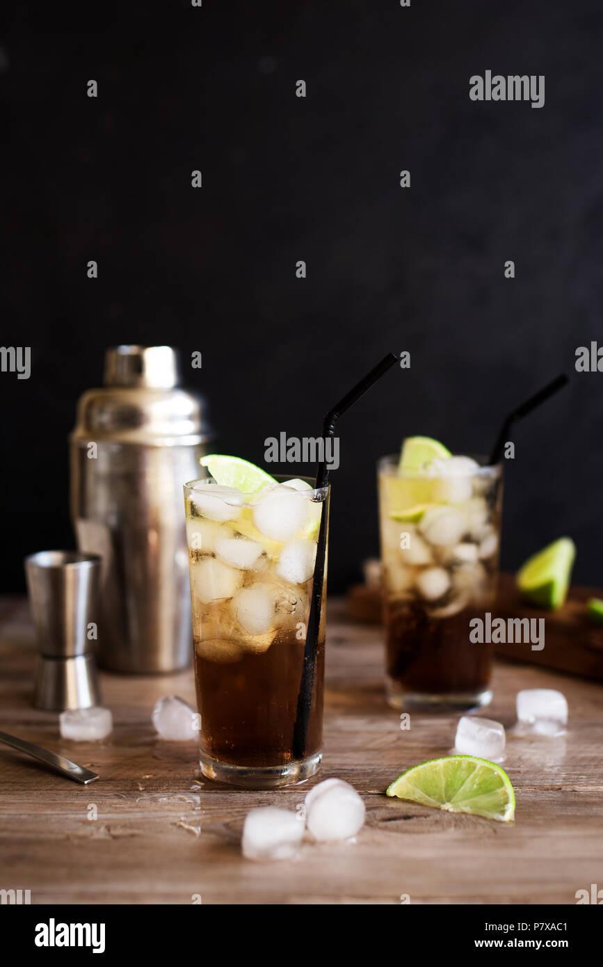 Rum und Cola Cuba Libre trinken mit Kalk und Eis auf rustikalen Holztisch Stockbild