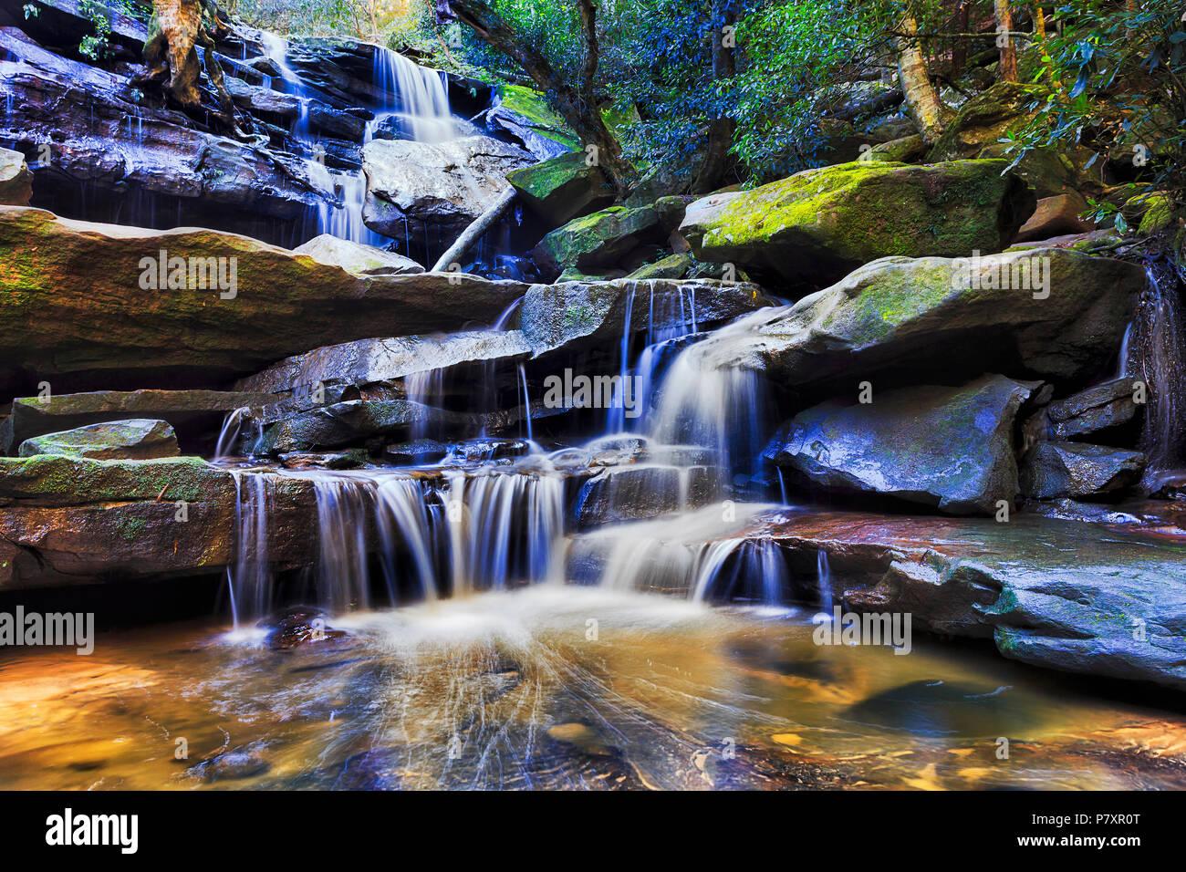Glatte, fließende Wasserfall Kaskade von Sandsteinfelsen im tiefen Regenwald Creek in der Nähe von SOmersby auf australischen Central Coast. Stockbild