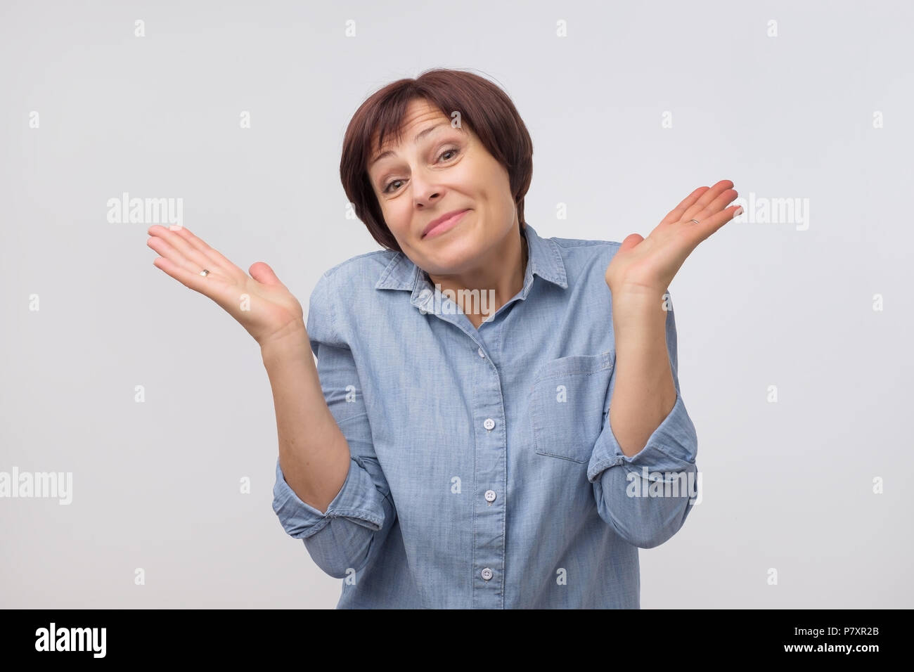 Zuckend reife Frau im Zweifel an Kamera suchen Stockbild