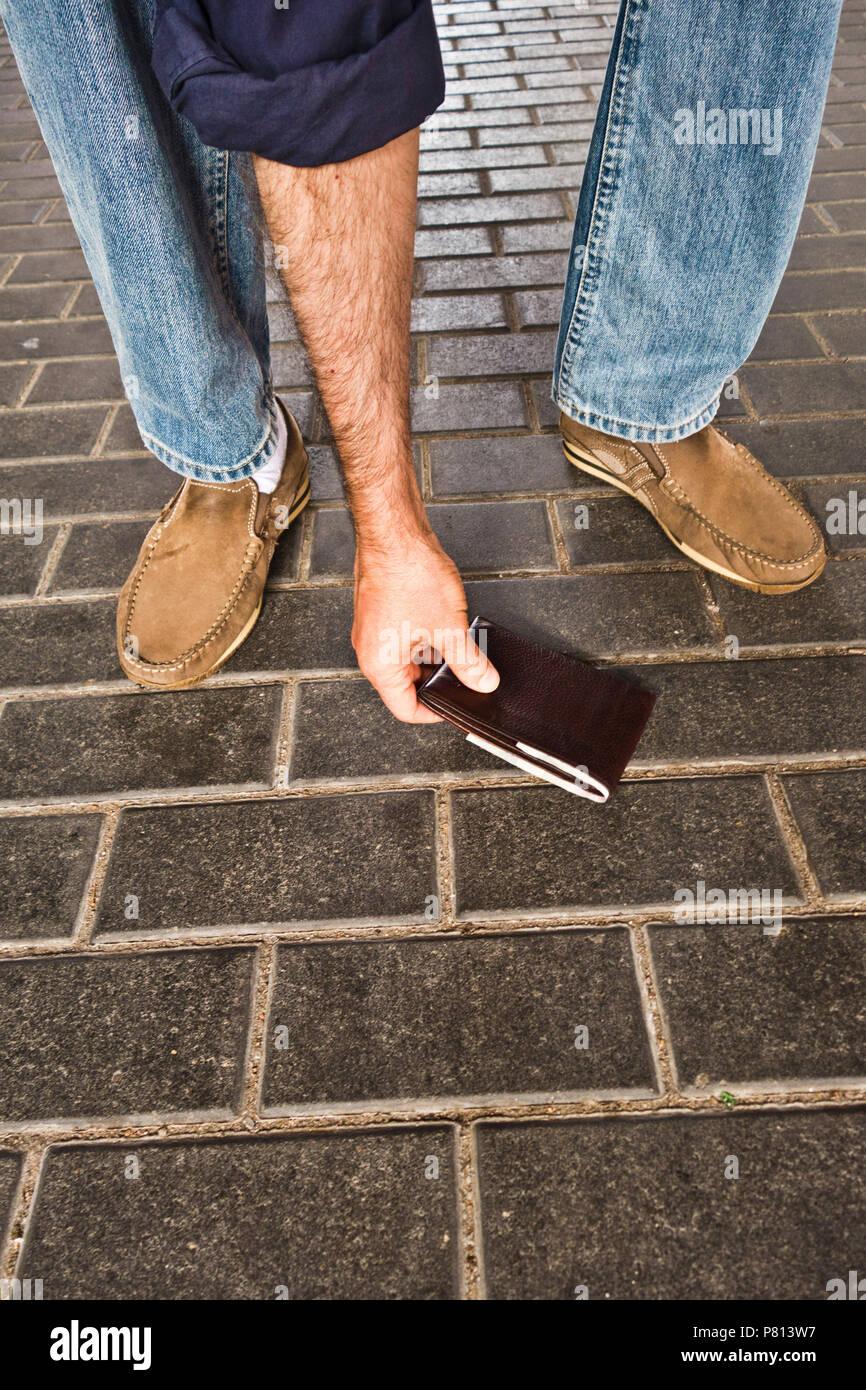 Mann, eine Brieftasche auf den Boden verloren und Picking it up Stockbild
