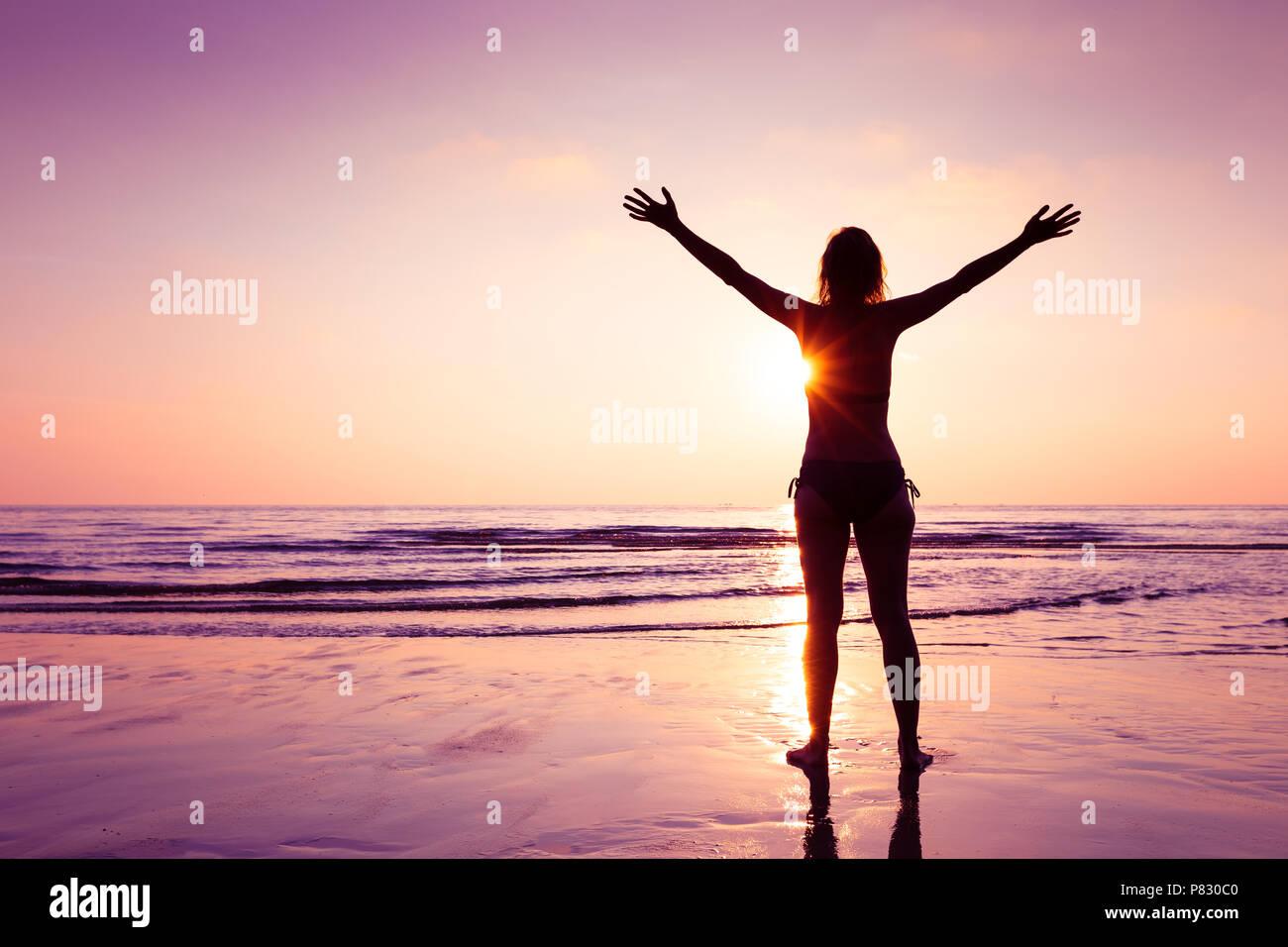 Gerne fröhliche Frau Verbreitung Hände am Strand bei Sonnenuntergang, freundliche Emotion und Achtsamkeit, Balance, eingedenk Denken Stockbild