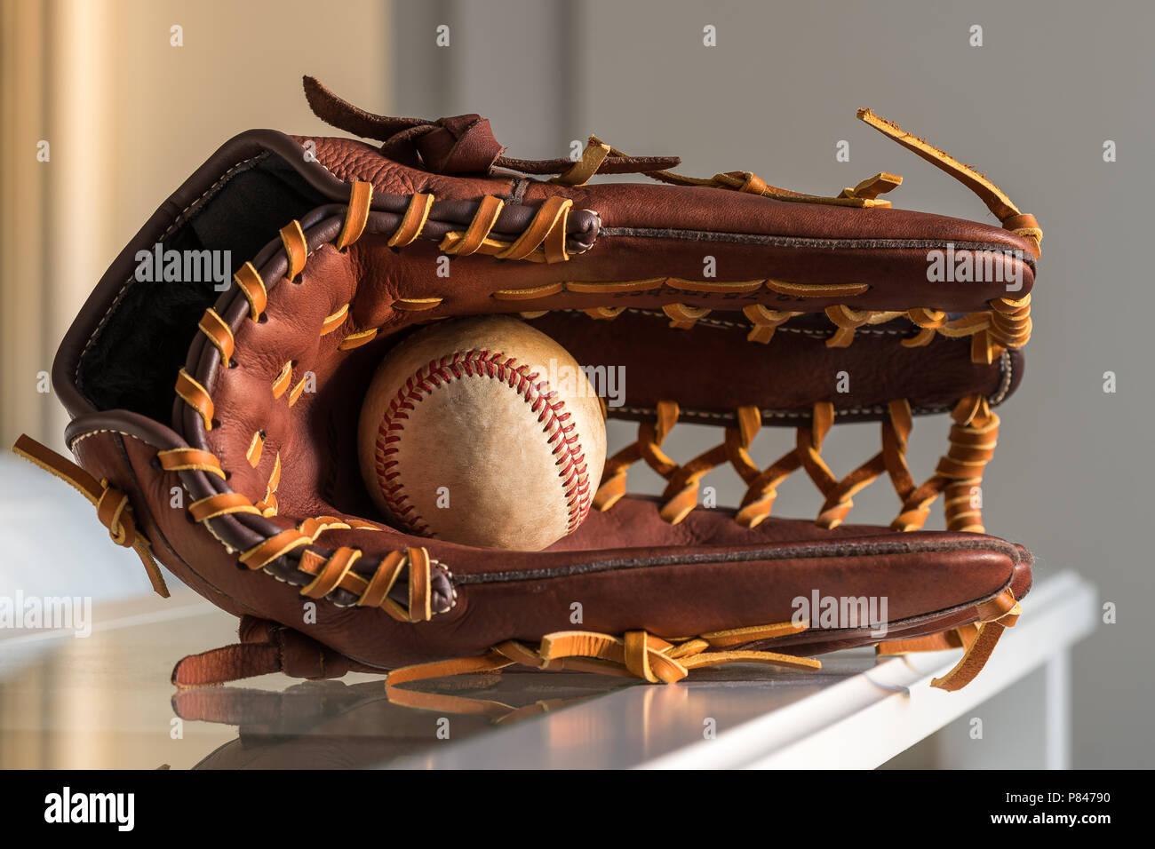 Nahaufnahme einer verwendet baseball ball innerhalb Braun, Leder baseball Handschuh auf schlichten, grauen Hintergrund. Stockfoto