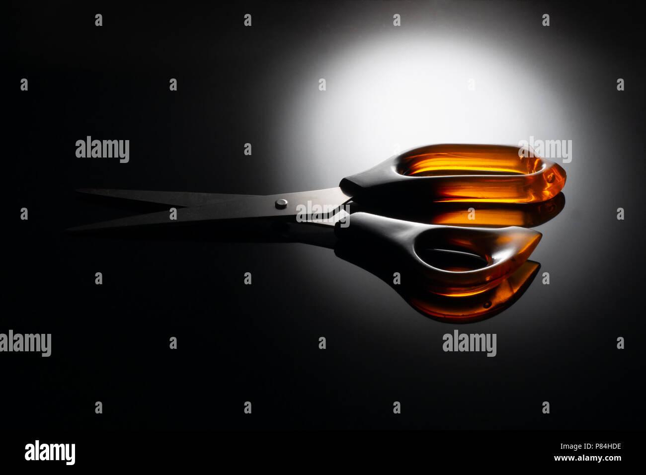 Griff aus Kunststoff Schere auf glänzende, reflektierende Schwarz Spiegel effekt. Dramatische Beleuchtung. Stockbild