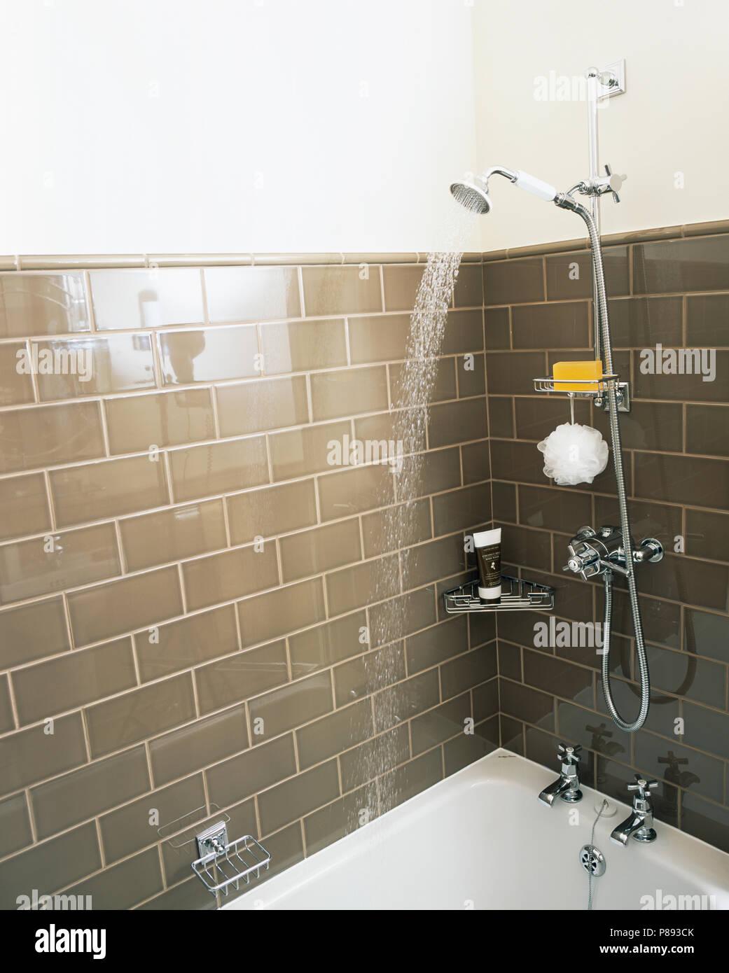 Chrom Dusche sprühen Wasser in die Badewanne in Braun Fliesen ...