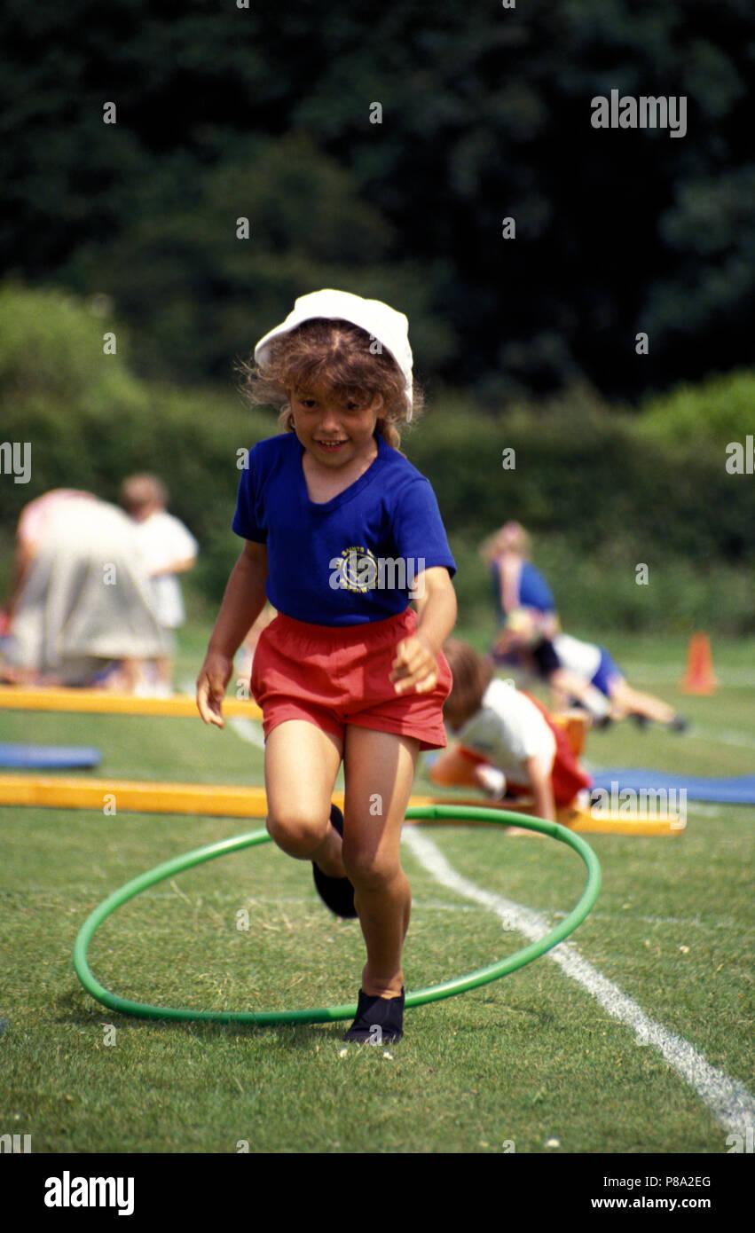 Kleine Mädchen die Teilnahme an Hindernis Rennen während der Grundschule Sport Tag Stockbild