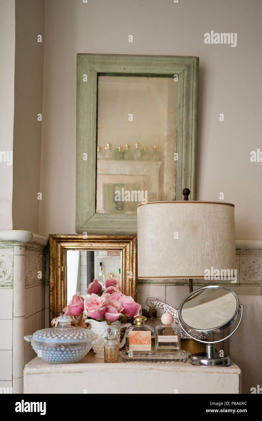 Eine Auswahl an Spiegeln und Parfüms auf Schrank in shabby ...