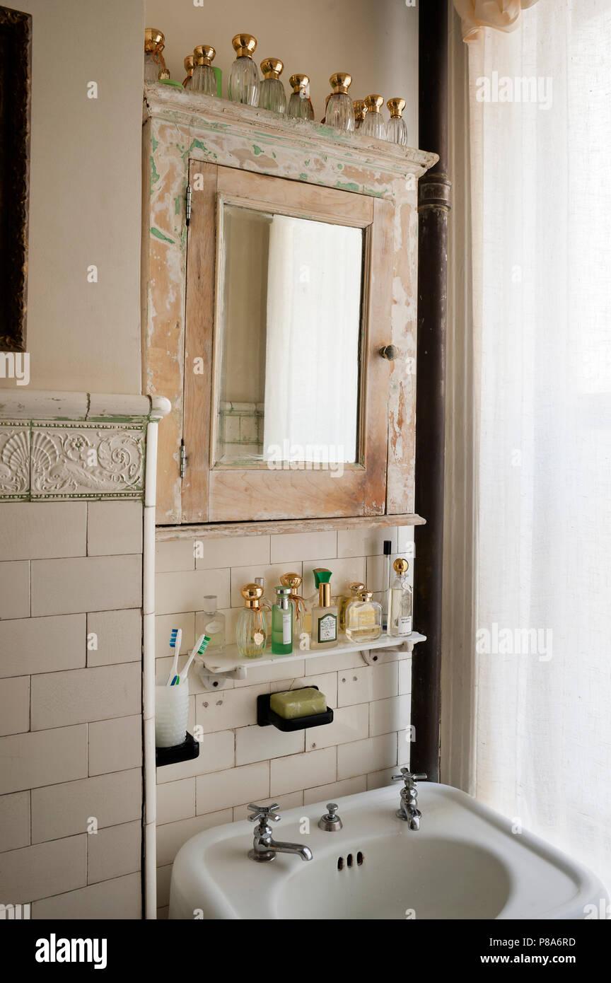 Alte Flakons aufgereiht entlang zurückgefordert Spiegelschrank in ...