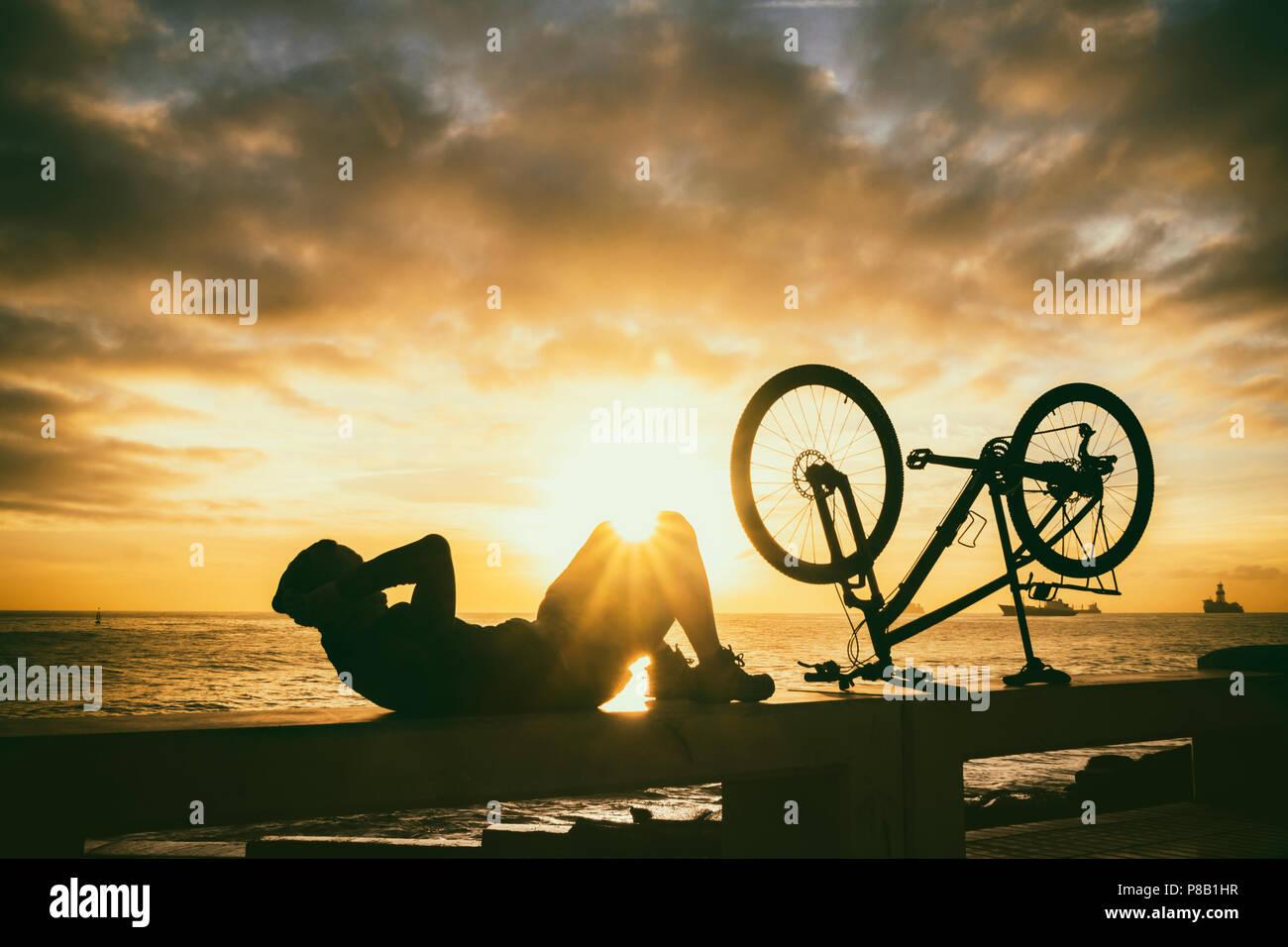 Männliche Mountainbiker tun Sit Ups auf Meer Wand an sunriise Stockbild