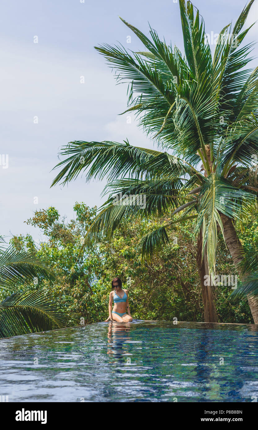 Attraktive Mädchen im Bikini am Pool mit Palmen rund um Stockbild
