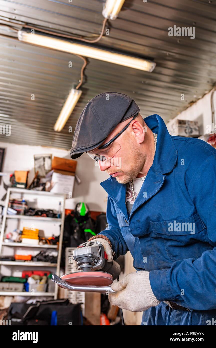 Ein junger Mann Schweißer in einem blauen T-Shirt, Schutzbrille und Handschuhe Prozesse Metall ein Winkelschleifer in der Garage, im Hintergrund eine Menge von Werkzeugen Stockbild