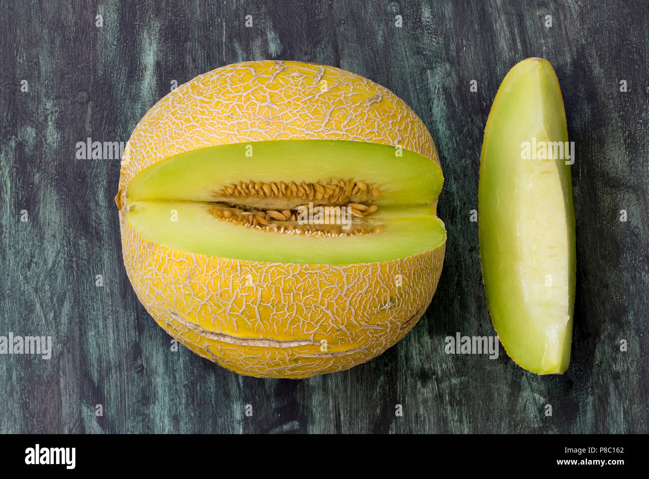 Frische Melone in kleine Stücke schneiden auf Holztisch. Direkt oben betrachten. Stockbild