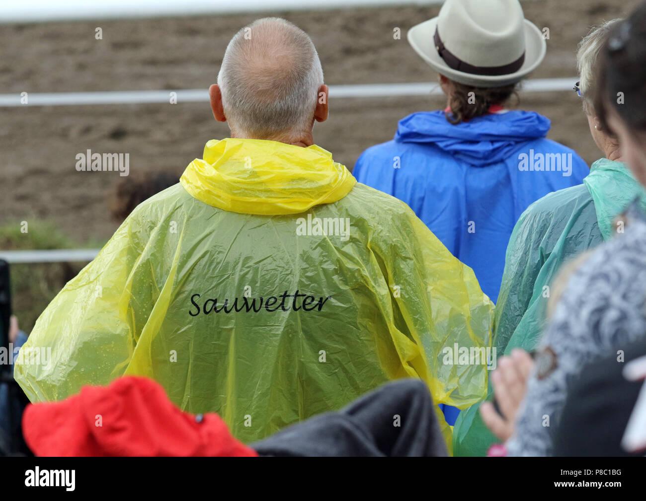 Ganschow, Deutschland, Mann trägt einen Regenmantel mit der Aufschrift Sauwetter Stockbild
