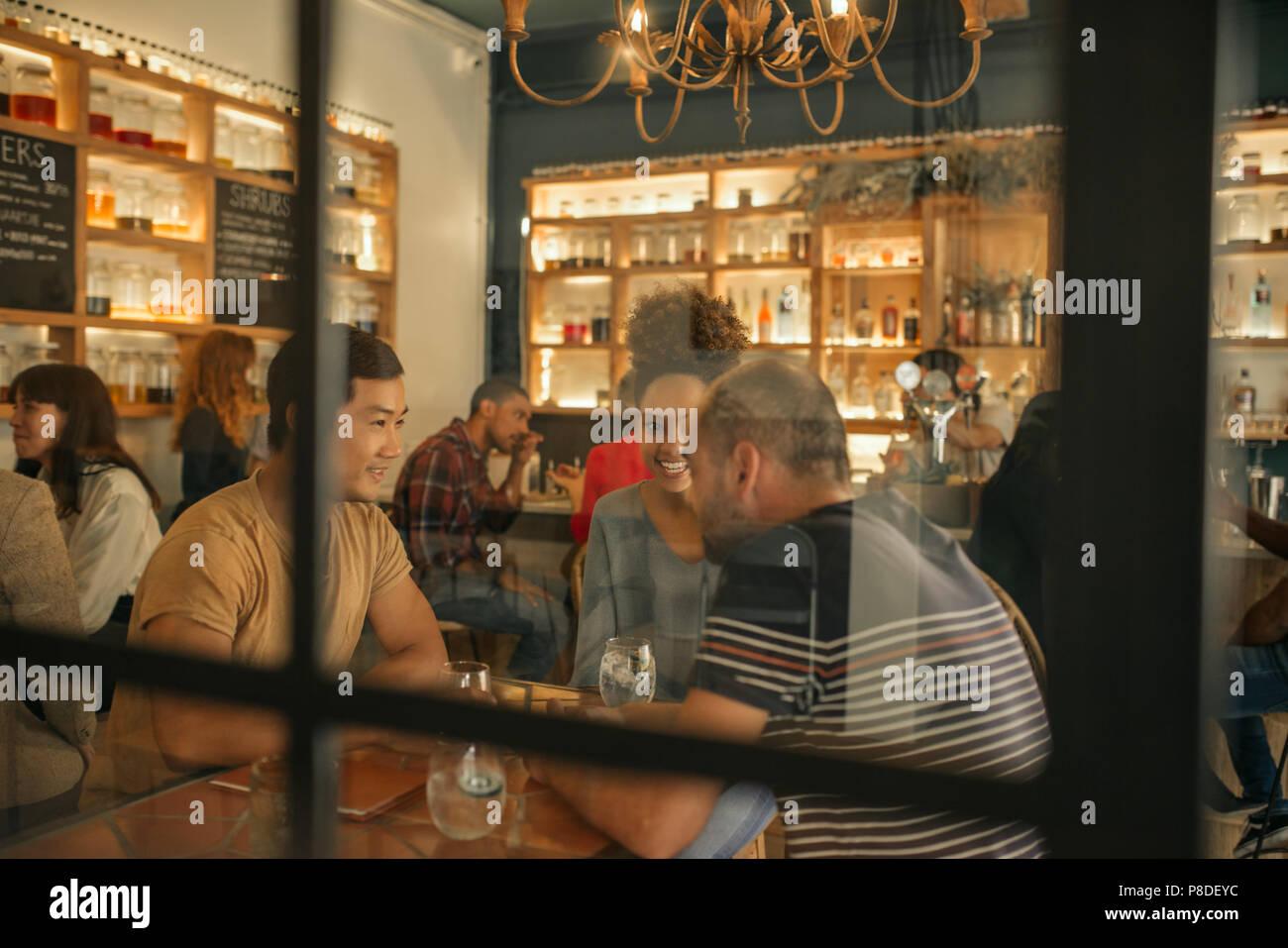 Lächelnden jungen Freunden in einer Bar zusammen zu sitzen Stockbild