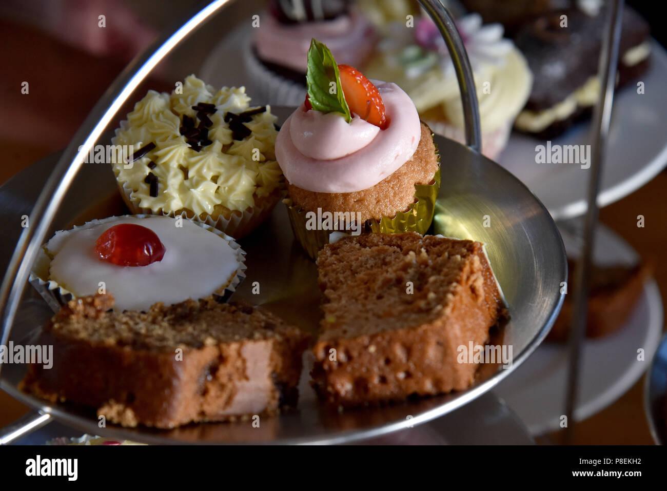 Bild zeigt einen Kuchen stand mit Torten, einschließlich einer Tasse Kuchen, eine Scone, Datum und Walnuss Kaffee und einem Stück Kuchen Stockbild