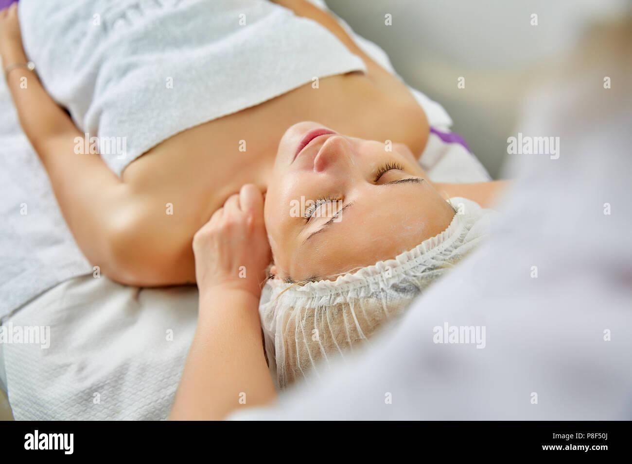 Schöne junge Frau liegend auf Massageliege während natürliche Gesichtsmaske ist auf Ihrem Gesicht angewendet Stockbild