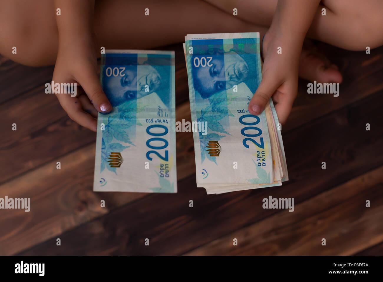 Kind zählt Geld, Nahaufnahme, israelische Schekel Stockbild