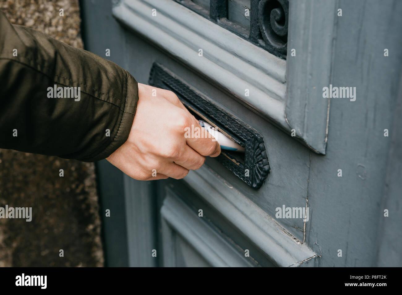 Der Postbote bringt einen Brief oder eine Zeitung oder Zeitschrift in der Mailbox an der Tür eines Wohnhauses oder einer Person stellt eine Broschüre mit Werbung. Stockbild