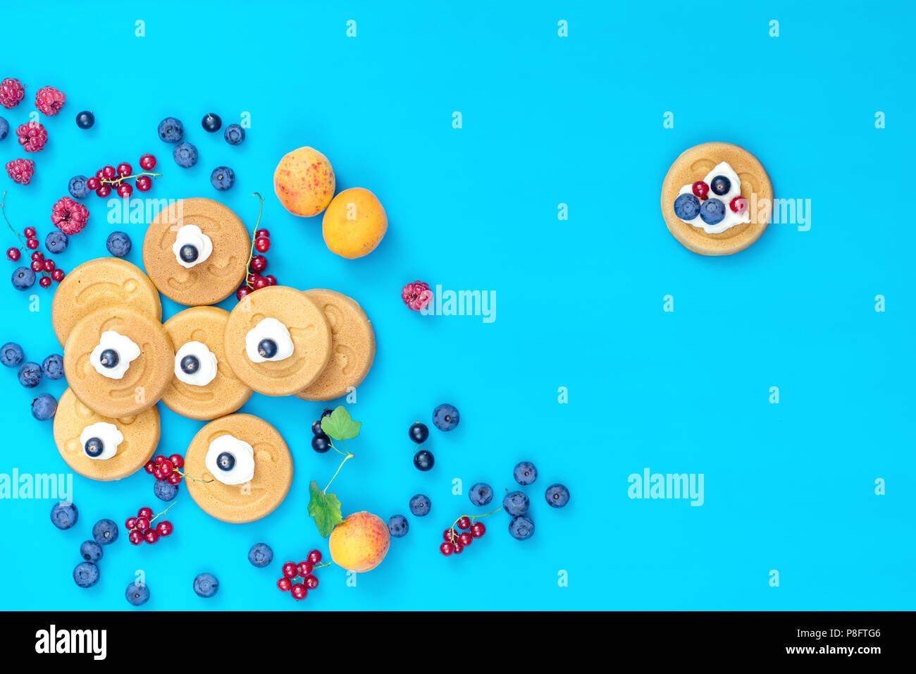 Leckere mini smile Pfannkuchen mit Beeren auf blaue Fläche, Ansicht von oben. Flach, Ansicht von oben süße Speisen Hintergrund. Stockbild