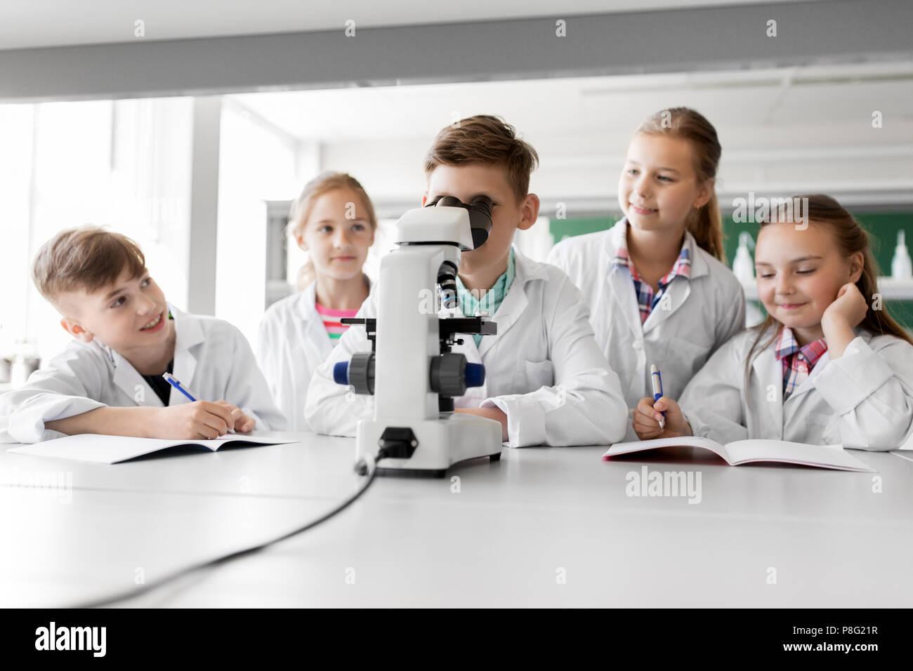Kinder schüler oder studenten mit mikroskop biologie in der schule