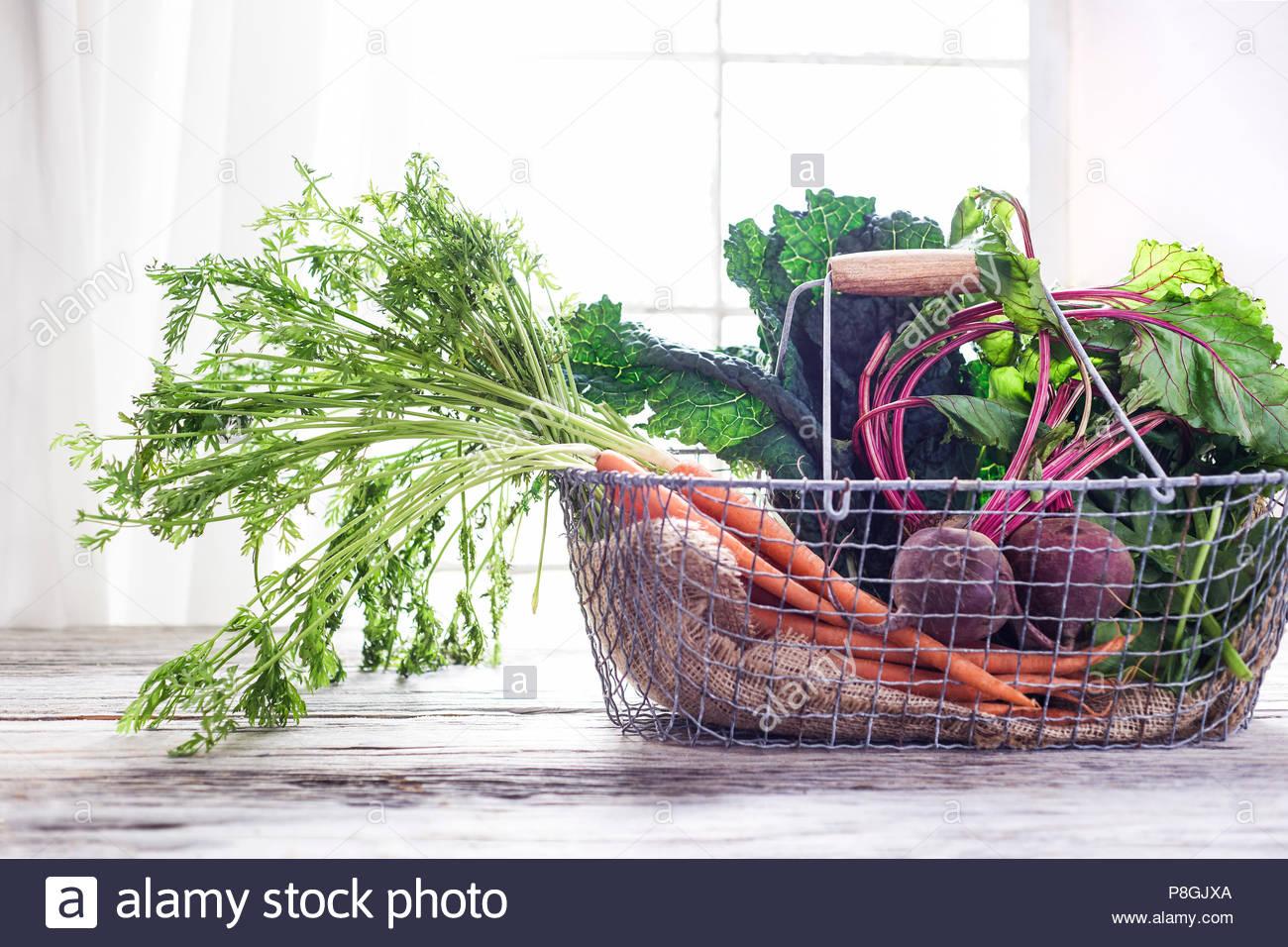 Ein rustikales, Metall Korb gefüllt mit frischem Gemüse auf einem Holz Tisch abgeholt. Helle Hintergrundbeleuchtung. Stockbild