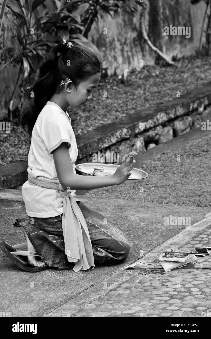 Eine balinesische Mädchen macht Hindu-Angebote in das traditionelle Dorf PENGLIPURAN - BALI, Indonesien Stockbild
