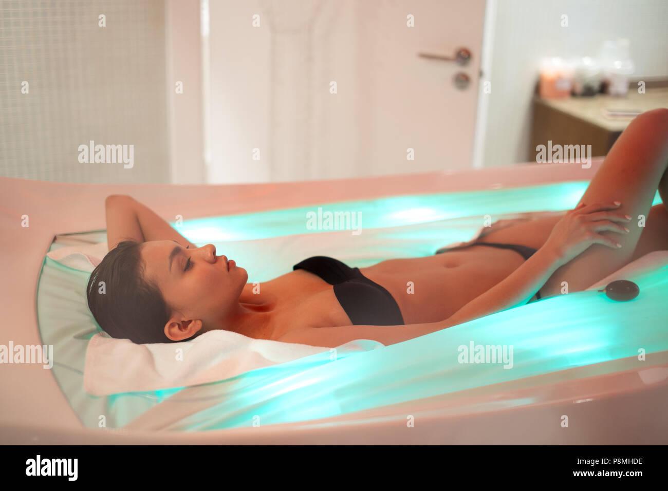 Wirkung von Licht auf den Organismus. junge Frau mit Massage mit Beleuchtung Stockbild