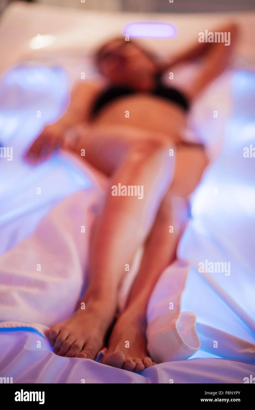 Junge Frau im schwarzen Badeanzug liegen auf der Farbtherapie. Gefühl der Zufriedenheit. verschwommenes Foto Stockbild