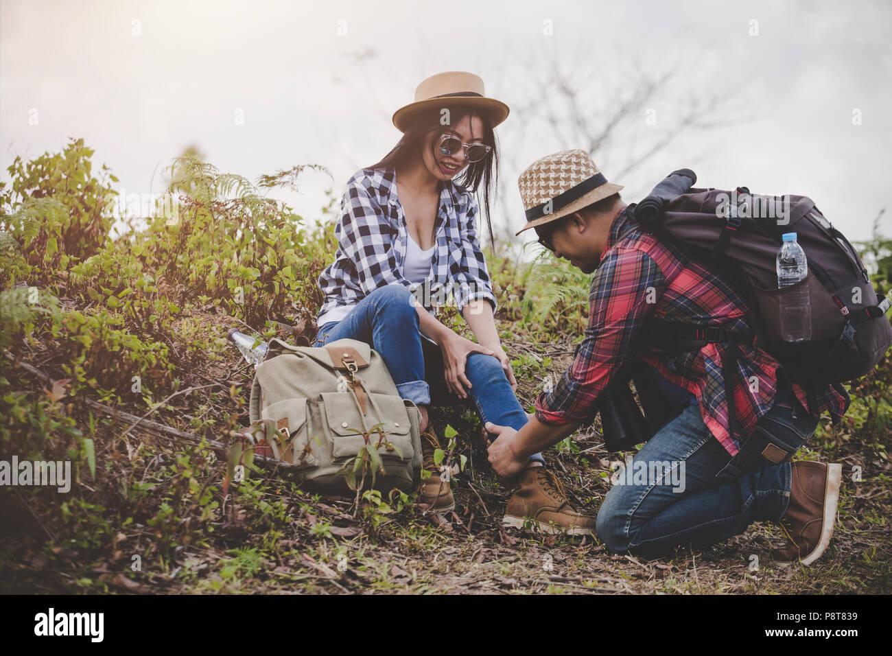 Asiatische junge Paar Reisende zu wandern Knöchelverletzung auf grünem Hintergrund, Wandern Konzept. Stockfoto