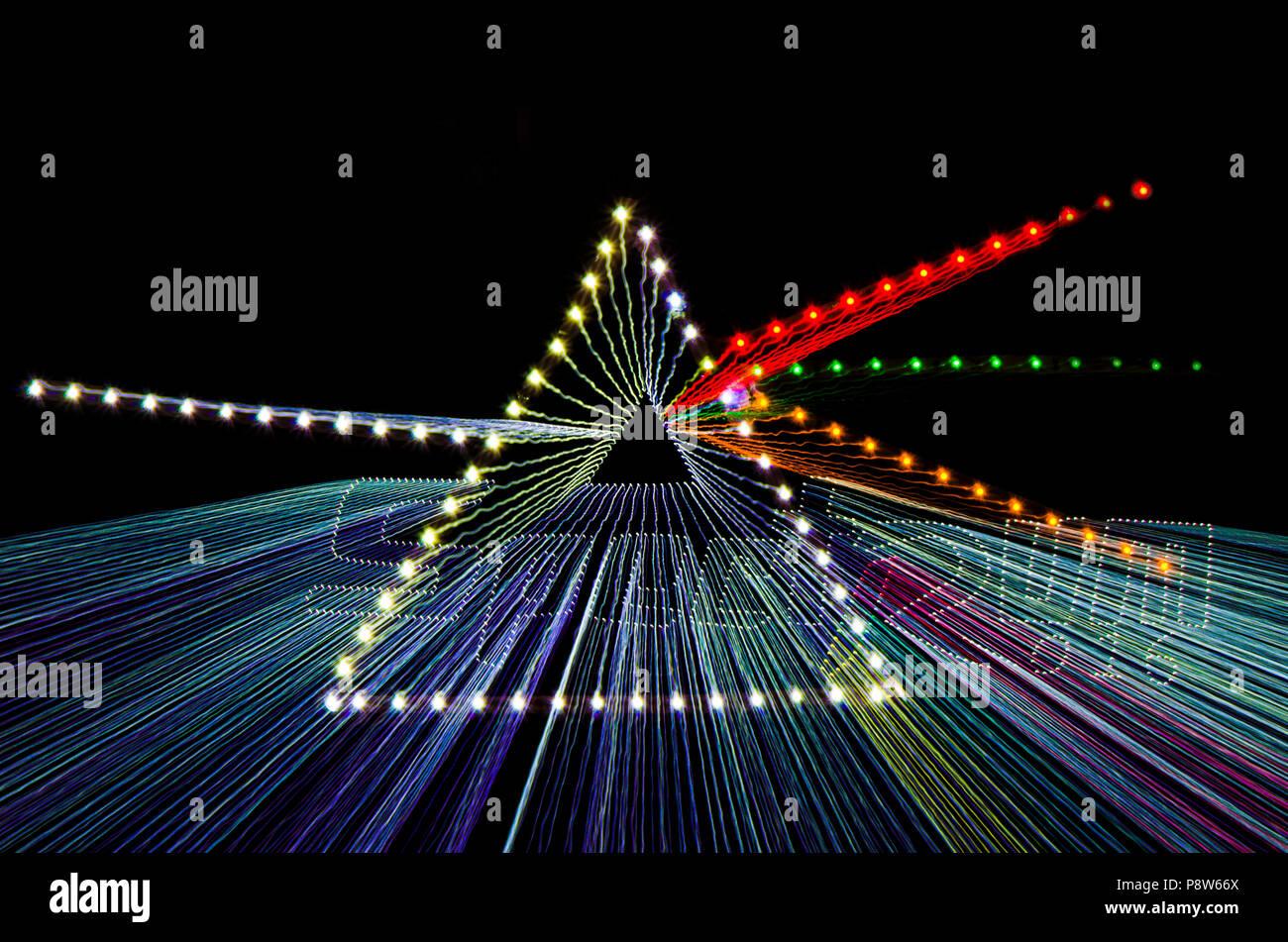 Zoom Burst, trügerische Bild der Begriff der Dispersion weißes Licht durch ein Prisma mit unterschiedlichen Farbe präsentiert LED-Glühbirnen über schwarzen Hintergrund. Stockbild