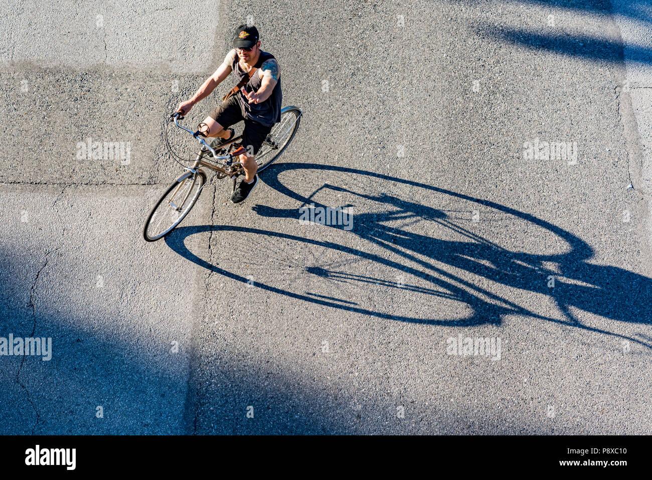Radfahrer und lange Schatten, Vancouver, British Columbia, Kanada. Stockbild