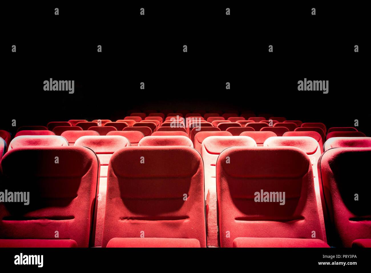 Dunklen Kinosaal mit Projektion, Licht und Leere rote Sitze Stockbild
