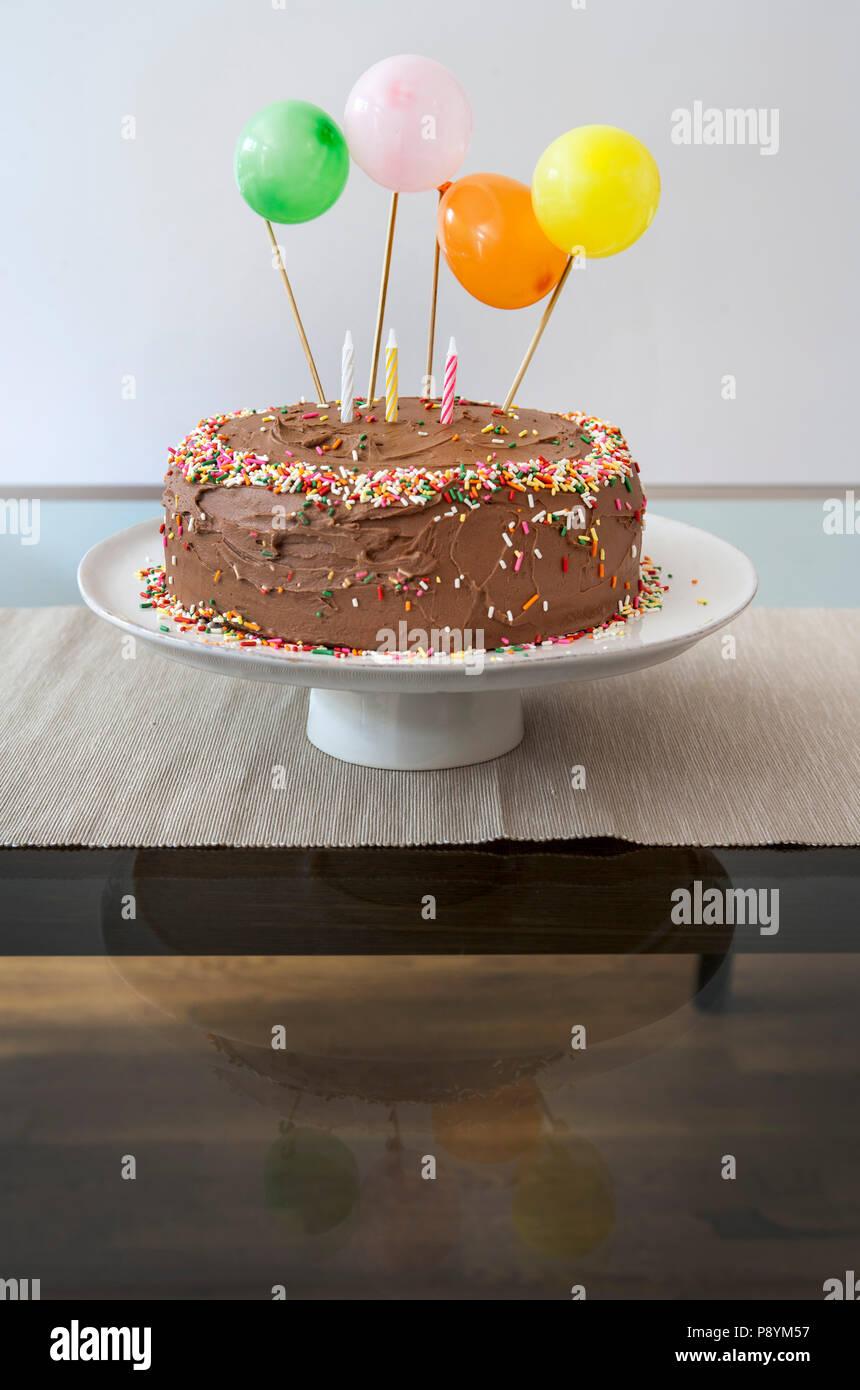 Geburtstag Kuchen mit Schokoladenglasur dekoriert mit Ballons, besprüht und Kerzen Stockbild